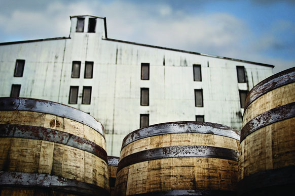 A group of barrels sitting outside a Brown-Forman distillery