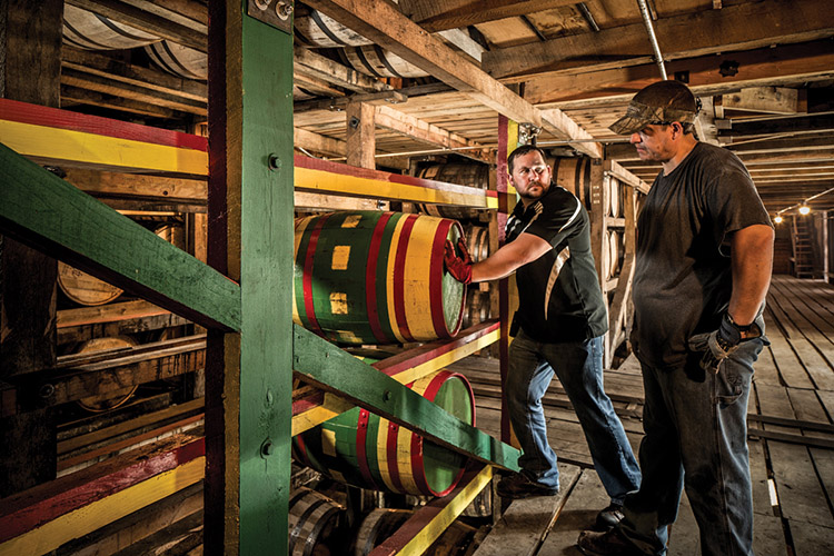 Two Brown-Forman employees demonstrating hand safety while moving barrels